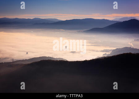 Scenic view of cloudscape over landscape - Stock Image