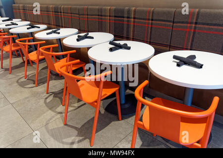 Circular white cafe tables and chairs in a restaurant - Stock Image