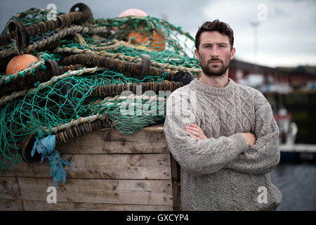 Portrait of young fisherman leaning against crate of fishing nets in harbour, Fraserburgh, Scotland - Stock Image