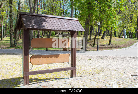 wooden sign boards in the city park on sunny summer day - Stock Image