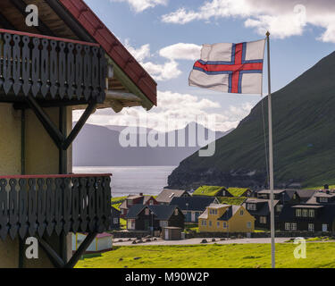 Faroese flag flying in the breeze above the village of Gjógv in the Faroe Islands, Denmark. Summer (June) 2017. - Stock Image