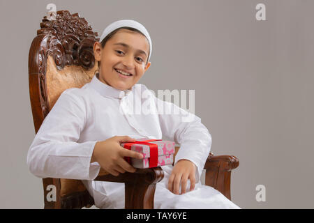 portrait of a Muslim Boy Holding Present - Stock Image