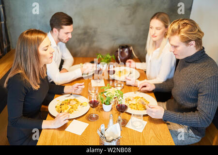 Young people having lunch together or having dinner in the restaurant - Stock Image