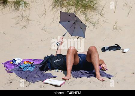 Camber, East Sussex, UK. 19th Apr, 2019. A hot and sunny start to the bank holiday weather on the South East coast with temperatures expected to exceed 24c in some parts of the country. Camber Sands in East Sussex is packed full of people making the most of the lovely day. A man shields himself from the hot sun with a baby umbrella. Credit: Paul Lawrenson 2019, Photo Credit: Paul Lawrenson/Alamy Live News - Stock Image