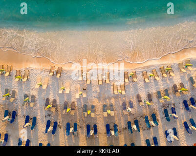 Sunbeds and umbrellas on the beach at sunrise in Thasos, Greece - Stock Image