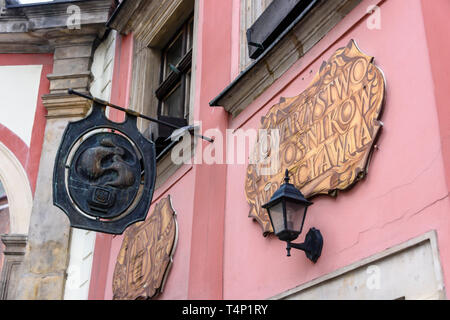 Cast iron plaque and painted signs outside a very old pub, Wrocław, Wroclaw, Wroklaw, Poland - Stock Image