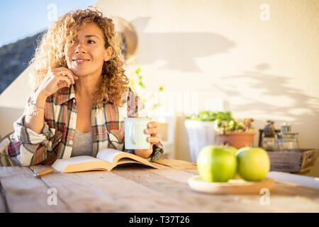 Cheerful relaxed beautiful curly blonde caucasianwoman enjoy the sunny day at home on the terrace reading a book and drinking tea or coffee from a mug - Stock Image