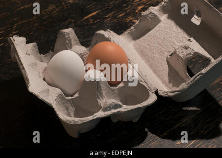 brown and white eggs in egg container - Stock Image