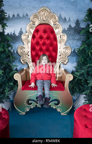 Portrait of four years old child with red coat looking at and sitting on a golden throne, in winter christmas holidays - Stock Image