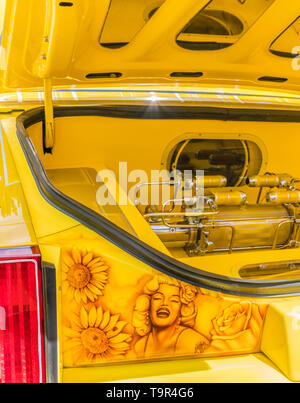 A detail of the trunk of a bright yellow Chevrolet lowrider car that has been completely customized with a airbrush painted image of Marilyn Monroe on - Stock Image