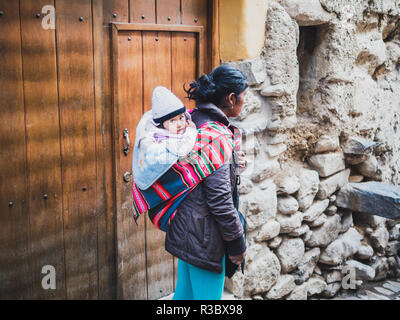 Ollantaytambo, Peru - January 5, 2017. A woman carrying her baby in the traditional way in the Ollantaytambo streets - Stock Image