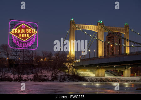Historic Grain Belt Beer sign and Hennepin Avenue bridge along the Mississippi River in downtown Minneapolis, Minnesota. The sign is lit in Purple and - Stock Image