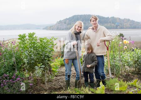 Portrait of couple and son digging organic garden, Orust, Sweden - Stock Image