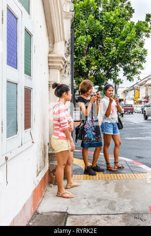 Phuket, Thailand - 11th April 2017: Young Asian tourists taking photos. The old town is very photogenic. - Stock Image