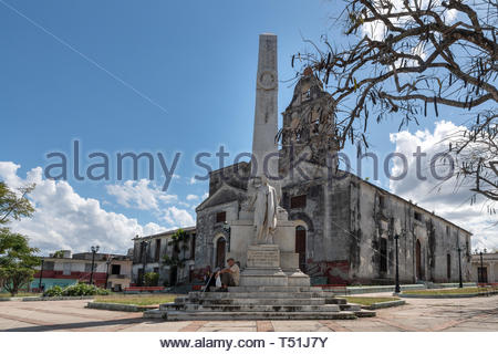 White marble monument honoring Miguel Jeronimo Gutierrez in the 'La Pastora' park. The Catholic church of the same name is in the background. Miguel w - Stock Image