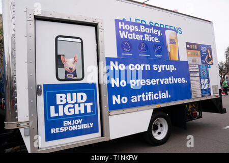 A trailer plastered with signs for Bud Light beer parked on the street adjacent to a parade through downtown Laredo, Texas - Stock Image