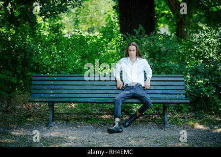 Portrait confident young man sitting on park bench - Stock Image