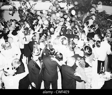Revelers trying to catch balloons falling from the ceiling on New Year's Eve at The Patio, Palm Beach, Florida, - Stock Image