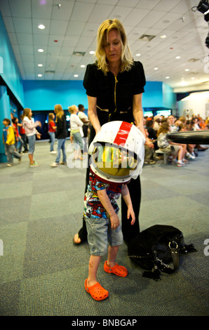 Three year old boy trying on a heavy astronaut helmet , space centre, Houston, Texas, U.S.A - Stock Image