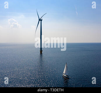 WindTurbines in a blue sea on a sunny day with a sailing boat passing by - Stock Image