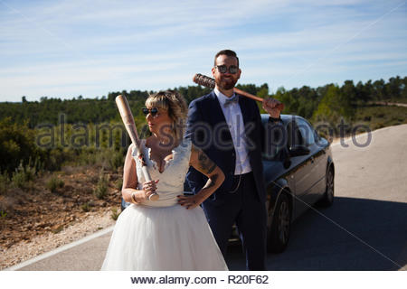 Couple of newlyweds stopped with the car on a lonely road wielding baseball bats - Stock Image