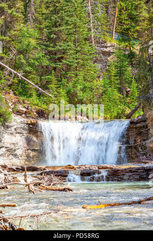 Waterfall flowing into the turquoise colored Johnston Canyon creek at Banff National Park in Alberta, Canada. The waters empty into the Bow River. - Stock Image
