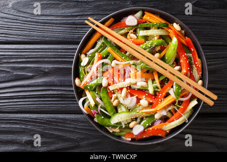 Salad of cucumbers, peppers, carrots, pea pods with sesame and peanuts close-up on a plate on the table. horizontal top view from above - Stock Image