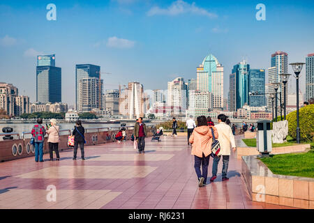 1 December 2018: Shanghai, China - Visitors walking on the bank of the Huangpu River on the Pudong side, opposite The Bund, Shanghai. - Stock Image
