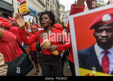 London, UK. 23rd August 2018. Hundreds of Ugandans, mainly dressed in red, protest at the Ugandan Embassy to say that President Museveni must go. They accuse him of being a dictator, and called for and end to the killing of opposition politicians and for  the release of those imprisoned, including business man, MP and singer Bobby Wine (Robert Kyagulanyi Ssentamu), and an end to land grabbing. Credit: Peter Marshall/Alamy Live News - Stock Image