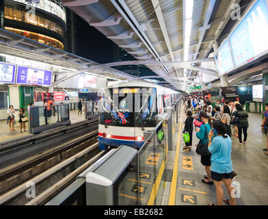 People waiting on a platform for a BTS sky train in Bangkok Thailand - Stock Image