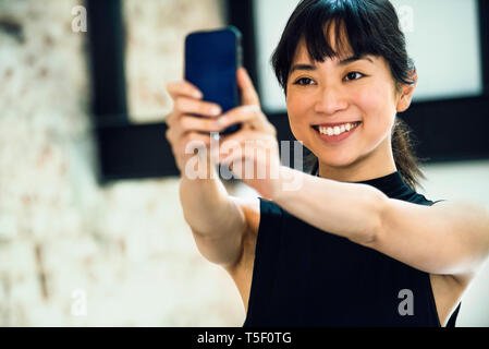 Businesswoman using smartphone - Stock Image