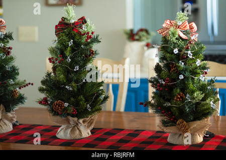 Three minature tabletop Christmas trees with burlap on a red and black table runner. Indoor Christmas decor. - Stock Image