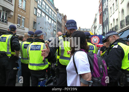 London, UK - 10 June 2018: A police officer grapples with a female pro Trump demonstrator by a FRee Tommy Robinson demo group  on 10 June 2018.  The Free Tommy Robinson were having a conter demonstraion to the Al Quads Day demonstraion outside the Saudi Arabian Embassy in  London. The annual event held on the last Friday of Ramadan that was initiated in 1979 to express support for the Palestinians and oppose Zionism and Israel. Credit: David Mbiyu Credit: david mbiyu/Alamy Live News - Stock Image