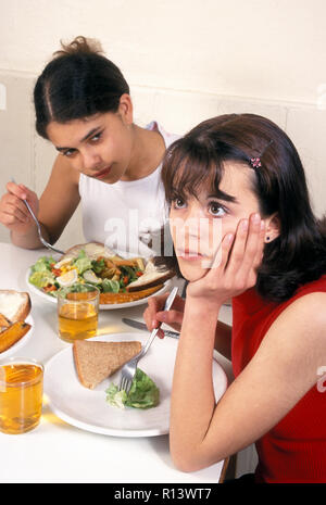 moody teenage girl with eating disorder sitting at dining table with friend - Stock Image