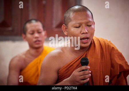 A Buddhist monk chanting with his eyes closed during a ceremony in one of the temples within their monastery. - Stock Image