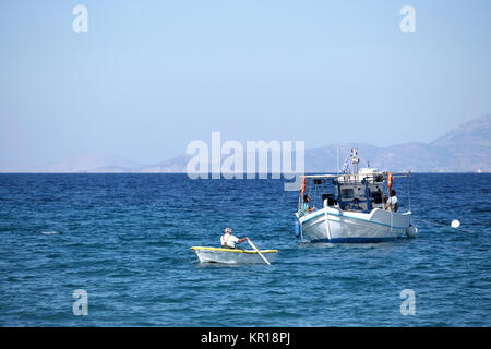 A local elderly fisherman rows to shore with a catch of freshly caught fry, small fish, to be sold immediately at - Stock Image
