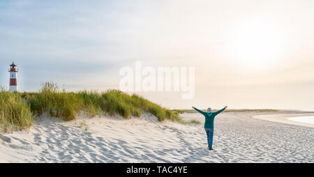 Germany, Sylt, North Sea, happy woman strolling on sandy beach - Stock Image