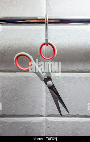 scissors hanging up in a kitchen - Stock Image