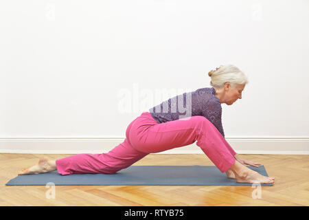 Senior woman with gray hair doing yoga exercise at home in front of a white wall, position dragon intro - Stock Image
