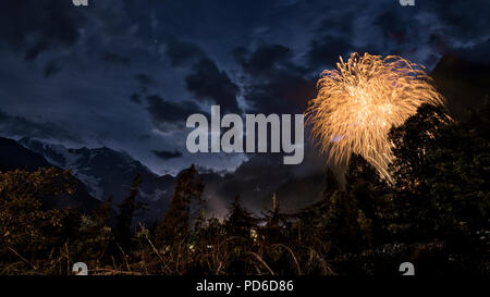 fireworks in the wood with East wall of Monte Rosa and mountains landscape in summer evening - Stock Image