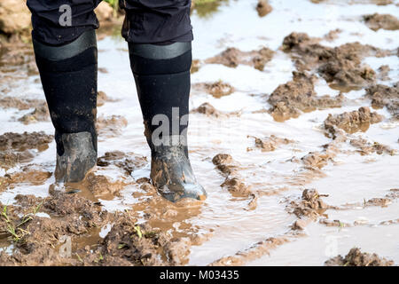 A female walking through thick mud on sodden wet ground. she is wearing wellington boots. the mud is ankle deep - Stock Image