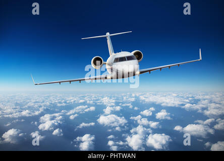 Luxury private jetliner flying above clouds. Modern and fastest mode of transportation, symbol of luxury and business traveling. - Stock Image