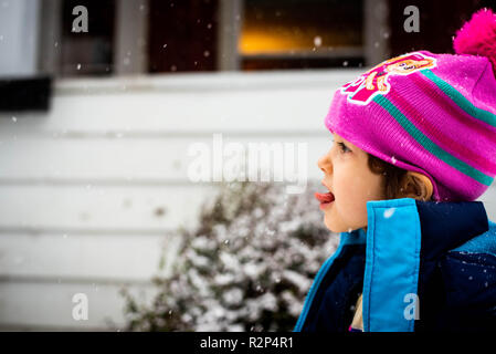 A little girl catches snowflakes on her tongue in the cold winter snow. - Stock Image