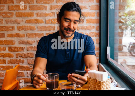 Mature man with black coffee using smart phone against brick wall in cafe - Stock Image