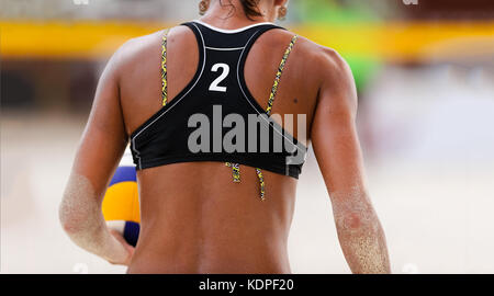 Volleyball beach is a female beach volleyball player getting ready to serve the ball . - Stock Image