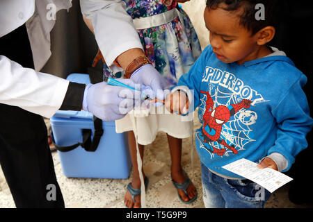 Sanaa, Yemen. 24th Apr, 2019. A medic puts a sign on the little finger of a child after he receives an anti-cholera vaccine against cholera in Sanaa, Yemen, on April 24, 2019. Yemeni Health Ministry in collaboration with WHO and UNICEF launched a 6-day home-to-home emergency immunization campaign against cholera in three most seriously affected districts in Sanaa with an aim to target all people from age of one year and above except pregnant women. Credit: Mohammed Mohammed/Xinhua/Alamy Live News - Stock Image