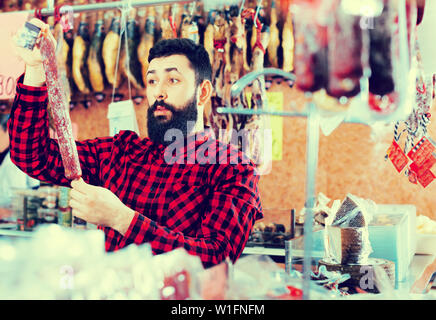 Smiling cheerful positive male customer examining sausages in butcher's shop - Stock Image