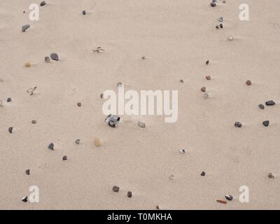 Sand of beach with soft waves and pebbles in warm sunny day at sea. Long walk along seaside. - Stock Image