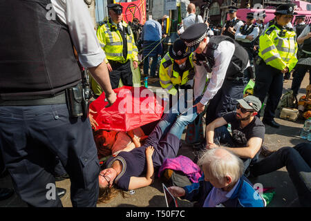 London, UK. 19th April 2019. Police grab the feet of a protester who has been arrested at at Extinction Rebellion's Sea of Protest after police surrounded the yacht and put a ring of officers around Oxford Circus. Police tried to persuade protesters to leave by threatening them with arrest. Later there were a number of arrests of protesters who refused to leave. A few tried to get the large crowd to protect the yacht, but XR organisers persuaded them not to physically oppose the police action. Peter Marshall/Alamy Live News - Stock Image