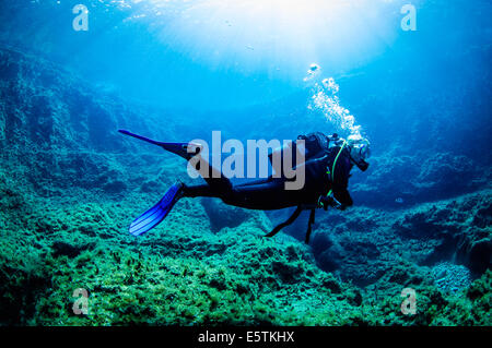 a young female diver near the surface and posing underwater while swimming over a limestone reef lit by rays of - Stock Image